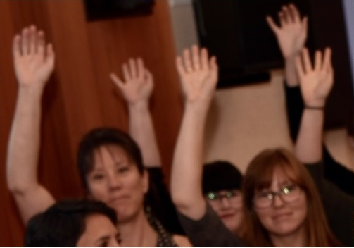 Staff members raising hands at Equity Alliance Meeting